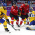 Simon Moser Photos - Johnny Oduya #27 of Sweden looks to clear the puck against Nino Niederreiter #22 and Simon Moser #82 of Switzerland in the first period during the Men's Ice Hockey Preliminary Round Group C game on day seven of the Sochi 2014 Winter Olympics at Bolshoy Ice Dome on February 14, 2014 in Sochi, Russia. - Winter Olympics: Ice Hockey
