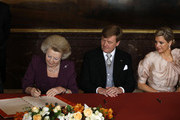 Queen Beatrix of the Netherlands signs of the Act of Abdication as her son Prince Willem-Alexander of the Netherlands and his wife Princess Maxima of the Netherlands (R) watches during a ceremony in the Moseszaal at the Royal Palace on April 30, 2013 in Amsterdam. Queen Beatrix of the Netherlands is abdicating the throne after a 33 year reign and hands the throne to her son Prince Willem-Alexander who will be sworn in later at the Nieuwe Kerk ahead of a joint session of parliament.