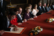 Mark Rutte signs the Act of Abdication as Queen Beatrix of the Netherlands (4th-L), her son Prince Willem-Alexander of the Netherlands (5th-L) and as his wife Princess Maxima of the Netherlands (6th-L) looks on during the abdication ceremony in the Moseszaal at the Royal Palace on April 30, 2013 in Amsterdam. Queen Beatrix of the Netherlands is abdicating the throne after a 33 year reign and hands the throne to her son Prince Willem-Alexander who will be sworn in later at the Nieuwe Kerk ahead of a joint session of parliament.