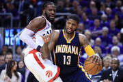 Paul George #13 of the Indiana Pacers dribbles the ball as DeMarre Carroll #5 of the Toronto Raptors defends in the first half of Game Two of the Eastern Conference Quarterfinals during the 2016 NBA Playoffs at the Air Canada Centre on April 18, 2016 in Toronto, Ontario, Canada.  NOTE TO USER: User expressly acknowledges and agrees that, by downloading and or using this photograph, User is consenting to the terms and conditions of the Getty Images License Agreement.