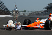 Dan Wheldon of England, driver of the #98 William Rast-Curb/Big Machine Dallara Honda, kisses the bricks next to the Borg Warner Trophy as his son Sebastian looks on, on the day after winning the IZOD IndyCar Series Indianapolis 500 Mile Race at the Indianapolis Motor Speedway on May 30, 2011 in Indianapolis, Indiana.