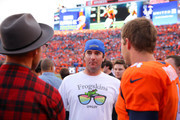 Bubba Watson, center, and Webb Simpson (left) have a word with Broncos punter Britton Colquitt #4 before a game between the Denver Broncos and the Indianapolis Colts at Sports Authority Field at Mile High on September 7, 2014 in Denver, Colorado.