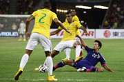 Luiz Gustavo Dias of Brazil and Taishi Taguchi of Japan challenge for the ball during the international friendly match between Japan and Brazil at the National Stadium on October 14, 2014 in Singapore.