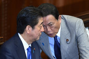 Japanese Prime Minister Shinzo Abe (L) chats with Finance Minister Taro Aso during a plenary session of the House of Representatives at the end of 150-day regular Diet session on June 1, 2016..Japanese leader Shinzo Abe is set to announce June 1 that he will delay a consumption tax hike and launch another blast of government spending, underscoring his failure to ignite the limp economy, analysts said. / AFP / KAZUHIRO NOGI