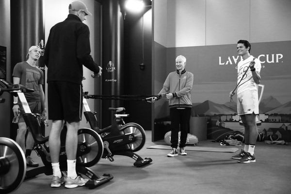 Laver Cup 2019 - Preview Day 4 [image,physical fitness,standing,vehicle,room,sports,sports training,bicycle,sports equipment,recreation,black-and-white,john mcenroe,john isner,captain of team world,players,milos raonic,denis shapovalov of team world,palexpo,laver cup,practice session]