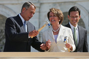 """Impatient with how long it was taking House Minority Leader Nancy Pelosi (D-CA) (R) to drive a nail, Speaker of the House John Boehner finishes the job with one stroke during the """"First Nail"""" ceremony, signifying the start of construction of the 2013 Inaugural Platform on the West Front of the U.S. Captiol September 20, 2012 in Washington, DC. House Majority Leader Eric Cantor (R-VA) is at right. The winner of the November 6 presidential election will be sworn in on the platform on January 21, 2013."""