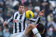 Andrea Barzagli (L) of Juventus FC competes with Joaquin Larrivey of Cagliari Calcio during the Serie A match between Juventus FC and Cagliari Calcio at Juventus Arena on January 15, 2012 in Turin, Italy.