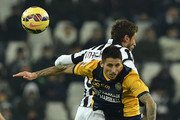 Claudio Marchisio (L) of Juventus FC clashes with Leandro Greco of Hellas Verona FC during the Serie A match between Juventus FC and Hellas Verona FC at Juventus Arena on January 18, 2015 in Turin, Italy.
