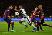 Patrice Evra of Juventus takes on Gerard Pique (L), Sergio Busquets and Daniel Alves (R) of Barcelona during the UEFA Champions League Final between Juventus and FC Barcelona at Olympiastadion on June 6, 2015 in Berlin, Germany.