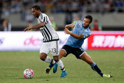Patrice Evra (L) of Juventus FC contests the ball against Felipe Anderson (R) of Lazio during the Italian Super Cup final football match between Juventus and Lazio at Shanghai Stadium on August 8, 2015 in Shanghai, China.