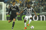 Patrice Evra (R) of Juventus FC is challenged by Cristiano Ronaldo (L) of Real Madrid CF during the UEFA Champions League semi final match between Juventus and Real Madrid CF at Juventus Arena on May 5, 2015 in Turin, Italy.