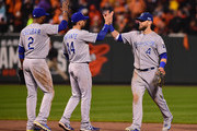 Alex Gordon #4 of the Kansas City Royals celebrates with his teammates Omar Infante #14 and Alcides Escobar #2 after defeating the Baltimore Orioles 8 to 6 in Game One of the American League Championship Series at Oriole Park at Camden Yards on October 10, 2014 in Baltimore, Maryland.
