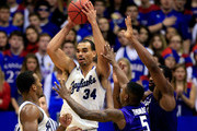 Perry Ellis #34 of the Kansas Jayhawks looks to pass as Jevon Thomas #5 and Thomas Gipson #42 of the Kansas State Wildcats defend during the game at Allen Fieldhouse on January 11, 2014 in Lawrence, Kansas.