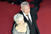 """French director Tonie Marshall (L) and French fashion designer Jean-Paul Gaultier pose as they arriveon May 15, 2016 for the screening of the film """"Mal de Pierres (From the Land of the Moon)"""" at the 69th Cannes Film Festival in Cannes, southern France.  / AFP / LOIC VENANCE"""