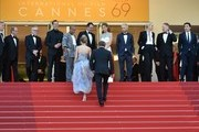 """(FromL) US actor and director Sean Penn (R) and his daughter Dylan Frances Penn (L) walk up the steps to join (From 2ndL) Festival President Pierre Lescure, Festival General Delegate Thierry Fremaux, US producer Matt Palmieri, US actor Zubin Cooper, French actor Jean Reno, French actress Adele Exarchopoulos, Sean Penn's son Hopper Jack Penn, South African-US actress Charlize Theron, British actor Jared Harris and Spanish actor Javier Bardem as they arrive on May 20, 2016 for the screening of the film """"The Last Face"""" at the 69th Cannes Film Festival in Cannes, southern France.  / AFP / ALBERTO PIZZOLI"""