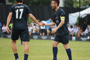Hidetoshi Nakata of Team Laureus shakes hands with Jari Litmanen (17) as he scores a goal during the Laureus All Stars Unity Cup ahead of the 2014 Laureus World Sports Awards at Royal Selangor Club on March 25, 2014 in Kuala Lumpur, Malaysia.