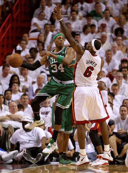 Paul Pierce of the Celtics passed the ball around Lebron James of the Heat.