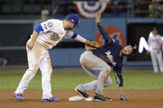 Ryan Braun #8 of the Milwaukee Brewers signals timeout to the second base umpire after safely stealing second base as Brian Dozier #6 of the Los Angeles Dodgers keeps the tag on Braun during the tenth inning of Game Four of the National League Championship Series at Dodger Stadium on October 16, 2018 in Los Angeles, California.