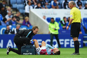 Carles Gil of Aston Villa is given treatment as referee Mike Dean looks on during the Barclays Premier League match between Leicester City and Aston Villa at the King Power Stadium on September 13, 2015 in Leicester, United Kingdom.