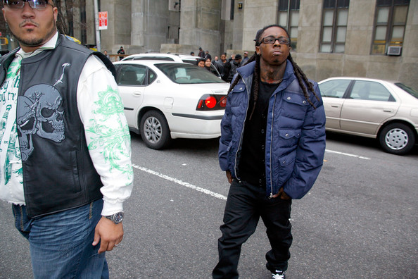 Lil Wayne (R) leaves court following a hearing for weapon charges at the New