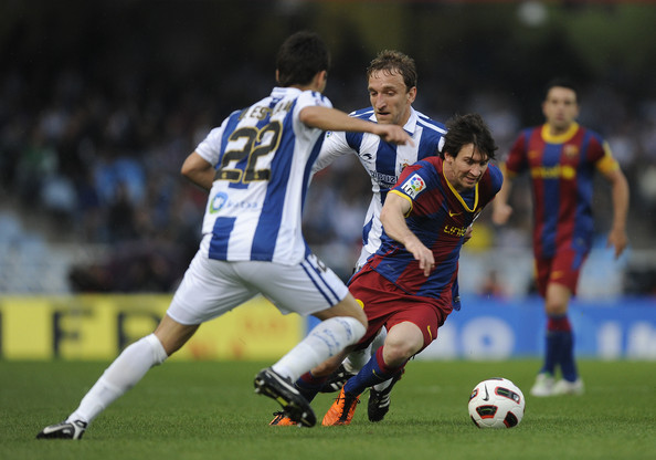 Lionel Messi Lionel Messi of FC Barcelona (R) fights for the ball against Diego Rivas of Real Sociedad (C) and Daniel Estrada of Real Sociedad during the La Liga match between Real Sociedad and Barcelona at Estadio Anoeta on April 30, 2011 in San Sebastian, Spain. Real Sociedad won 2-1.
