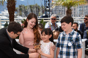 """(L-R) Director Mark Osborne, Mackenzie Foy, Rio Suzuki, and Riley Osborne attend a photocall for """"The Little Prince"""" during the 68th annual Cannes Film Festival on May 22, 2015 in Cannes, France."""