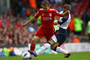 Leiva Lucas of Liverpool is tackled by Ivan Klasnic of Bolton Wanderers looks on during the Barclays Premier League match between Liverpool and Bolton Wanderers at Anfield on August 27, 2011 in Liverpool, England.