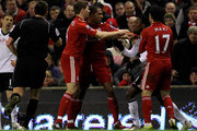John Pantsil of Fulham clashes with Steven Gerrard and Glen Johnson of Liverpool  during the Barclays Premier League match between Liverpool and Fulham at Anfield on January 26, 2011 in Liverpool, England.