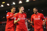 James Milner of Liverpool (C) celebrates with Roberto Firmino (L) and Emre Can (R) as he scores their first goal from a penalty during the Barclays Premier League match between Liverpool and Swansea City at Anfield on November 29, 2015 in Liverpool, England.