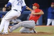 Raul Ibanez #28 of the Los Angeles Angels of Anaheim slides into home plate on a ball that got past the catcher before being tagged out in the fifth inning during MLB game action against the Toronto Blue Jays on May 9, 2014 at Rogers Centre in Toronto, Ontario, Canada.
