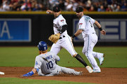 Ketel Marte #4 of the Arizona Diamondbacks turns a double play on a ground ball by Manny Machado #8 of the Los Angeles Dodgers as Justin Turner #10 slides into second base during the third inning at Chase Field on September 25, 2018 in Phoenix, Arizona.