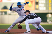 Carl Crawford #3 of the Los Angeles Dodgers leans back to first base as Justin Morneau #33 of the Colorado Rockies takes the pickoff throw in the first inning of a game   at Coors Field on September 26, 2015 in Denver, Colorado.