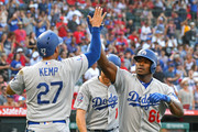 Yasiel Puig #66 of the Los Angeles Dodgers is greeted by Matt Kemp #27 and Logan Forsythe #11 after hitting a three-run home run in the second inning against the Los Angeles Angels of Anaheim at Angel Stadium on July 8, 2018 in Anaheim, California.