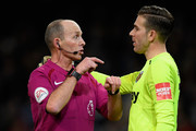 Referee Mike Dean (L) and Adrian of West Ham United (R) speak during the Premier League match between Manchester City and West Ham United at Etihad Stadium on December 3, 2017 in Manchester, England.