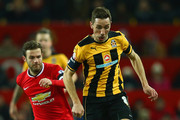 Tom Champion of Cambridge United breaks clear of Juan Mata of Manchester United during the FA Cup Fourth round replay match between Manchester United and Cambridge United at Old Trafford on February 3, 2015 in Manchester, England.