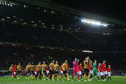 The captains Tom Champion of Cambridge United and Wayne Rooney of Manchester United lead the teams out during the FA Cup Fourth round replay match between Manchester United and Cambridge United at Old Trafford on February 3, 2015 in Manchester, England.