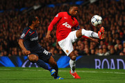 Patrice Evra of Manchester United competes with Leandro Salino of Olympiacos during the UEFA Champions League Round of 16 second round match between Manchester United and Olympiacos FC at Old Trafford on March 19, 2014 in Manchester, England.