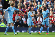 Joe Allen of Stoke City (C) celebrates scoring his sides first goal with his team mate Glen Johnson of Stoke City (R) during the Premier League match between Manchester United and Stoke City at Old Trafford on October 2, 2016 in Manchester, England.
