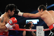 (R-L) Juan Manuel Marquez throws a left to the head of Manny Pacquiao during the WBO world welterweight title fight at the MGM Grand Garden Arena on November 12, 2011 in Las Vegas, Nevada.