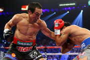 (L-R) Juan Manuel Marquez throws a left to the body of Manny Pacquiao during their welterweight bout at the MGM Grand Garden Arena on December 8, 2012 in Las Vegas, Nevada.