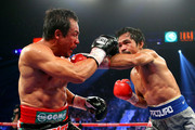 (R-L) Manny Pacquiao throws a left at Juan Manuel Marquez during their welterweight bout at the MGM Grand Garden Arena on December 8, 2012 in Las Vegas, Nevada.