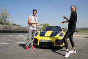 Porsche Brand Ambassadors Maria Sharapova and Mark Webber pose after driving with the high performance sports car Porsche 911 RT2 RS on the Weissach race track before the start of the Porsche Tennis Grand Prix tennis tournament on April 20, 2018 in Stuttgart, Germany.