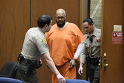 """Marion """"Suge"""" Knight  accompanied by Los Angeles Sheriff Deputies appears in Clara Shortridge Foltz Criminal Justice Center March 9, 2015 in Los Angeles, California. The hearing was scheduled to determine if the two criminal cases against Knight, one for murder and attempted murder when Knight allegedly ran over two men in a Compton parking lot after an argument and another case involving an alleged robbery and criminal threats to a photographer in Beverly Hills, should be moved to the downtown Los Angeles courthouse."""
