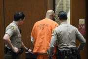 """Marion """"Suge"""" Knight (C) escorted by Los Angeles Sheriff Deputies after appearing for a hearing at the Clara Shortridge Foltz Criminal Justice Center March 9, 2015 in Los Angeles, California.  The hearing was scheduled to determine if the two criminal cases against Knight, one for murder and attempted murder when Knight allegedly ran over two men in a Compton parking lot after an argument and another case involving an alleged robbery and criminal threats to a photographer in Beverly Hills, should be moved to the downtown Los Angeles courthouse."""