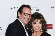 Dame Joan Collins and Percy Gibson arrive at a cocktail reception benefiting The Elizabeth Taylor AIDS Foundation at the Mark Zunino Atelier on November 07, 2019 in Beverly Hills, California.