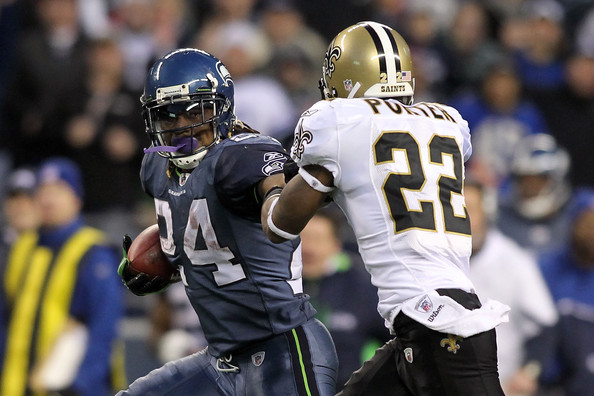 Marshawn Lynch tosses aside Jabari Greer on his way to a game-breaking 67-yard touchdown run. Photo by Jonathan Ferrey/Getty Images North America