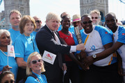 The Mayor of London, Boris Johnson (C) poses with the Commonwealth Games Queen's Baton with Faramolu Johnson and Michael Pusey and Olympic and Commonwealth Champion Christine Ohuruogu MBE (in Red) outside City Hall on June 6, 2014 in London, England. The Mayor of London, Boris Johnson welcomed the Commonwealth Games Queen's Baton to London after the two 'Batonbearers', Faramolu Johnson and Michael Pusey, accompanied by Olympic and Commonwealth Champion Christine Ohuruogu MBE delivered it to City Hall.