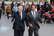 Mayor of London Boris Johnson (L) leaves City Hall with former Governor of California Arnold Schwarzenegger to ride London Cycle Hire bikes on March 31, 2011 in London, England. Mr Johnson has today met with Mr Schwarzenegger to exchange ideas on how to encourage low and zero emission technologies.