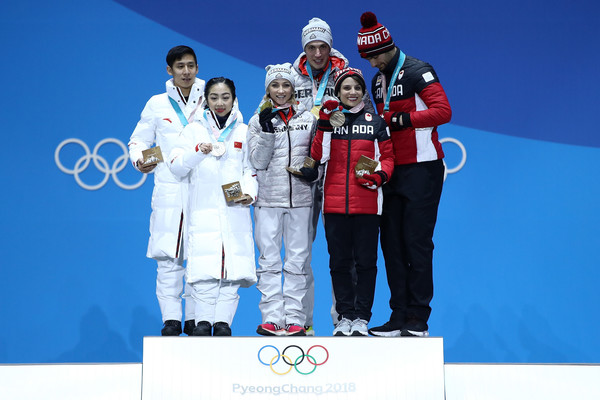 Medal Ceremony - Winter Olympics Day 6 [podium,technology,award,silver medal,electronic device,competition,stage equipment,team,recreation,medal,medalists,bronze medalists,cong han,wenjing sui,l-r,gold medalists,china,medal ceremony,winter olympics,medal ceremony]