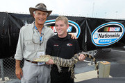 Jack Hanna of the Columbus Zoo and Justin Allgaier the driver of the Verizon Wireless Dodge are pictured with an alligator during the NASCAR Nationwide Series Meijer 300 presented by Ritz at Kentucky Speedway on June 12, 2010 in Sparta, Kentucky.